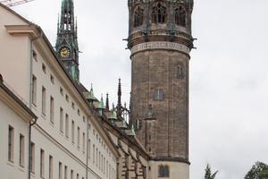 Der Kirchturm der neoromanischen Schlosskirche, dessen Haube und Spitze unentschieden zwischen einer Krone und einer Pickelhaube schwankt