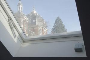 Schaut man vom Podest aus durch Dachfenster, das als RWA-Klappe fungiert, sieht man die Abteikirche von Burtscheid