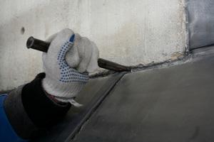 Verstemmen einer Fuge zwischen Metallblech und Mauerwerk mit Bleiwolle Foto: Saturnblei