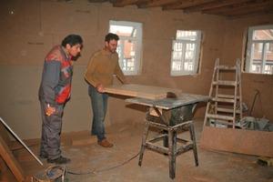 Die schmalen Plattenformate für den oberen Wandanschluss an die Decke schnitten die Handwerker mit der Tischkreissäge zu …<br />