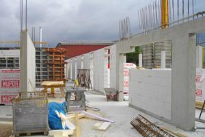 Rechts: Zur Optimierung der Dämmung mauerten die Rohbauer die Außenwandflächen zwischen dem Tragwerk mit Porenbetonsteinen