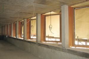 Ein gezacktes Fensterband holt Tageslicht in die Büroräume im Neubau und erweitert den Raum über die Gasse hinaus