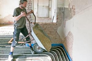 Oben: Einbringen der Lehm-Terrazzomasse mit der Schubkarre
