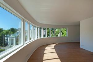Die dreifachverglasten Fenster folgen als Band dem Schwung der Außenwände<br />Fotos: Hanns Joosten