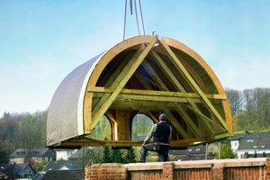 Mit dem Mobilkran wurden die beiden Hälften des neuen Turmhelms auf den aus Ziegeln gemauerten Turm gesetzt