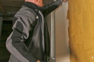 Aufziehen des Lehmmörtels auf die Wand. Dabei fällt einiges zu Boden<br />