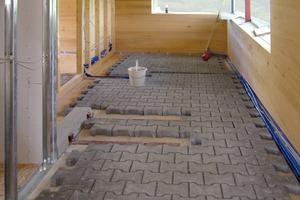 Auf die Holzelemente der EG-Decke verlegten die Handwerker aus Schallschutzgründen 6cm dicke, mit Quarzsand eingesandete Betonsteine<br />