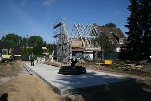 Die Bodenplatte für den Erweiterungsbau ist bereits betoniert. Ich Bildhintergrund sieht man die Arbeiten am Dach des Bestandsgebäudes<br />