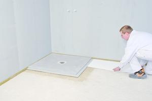 Auslegen der restlichen Fläche mit 10 mm dicken Dämmstoffplatten. Die Platten schließen mit dem Stufenfalz des Duschelements ab