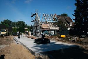 Links: Der Technikraum ist abgerissen, die linke Hälfte des Doppelhauses teilentkernt und fast alle Sparren für den neuen Dachstuhl schon aufgerichtet. Im Vordergrund ist die Bodenplatte für den Erweiterungsbau zu sehen<br />