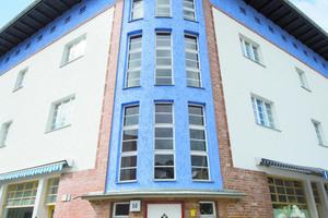 Helles, leuchtendes Blau bildet einen lebendigen Kontrast zum Weiß der Fassadenflächen und zum Rot der Klinker