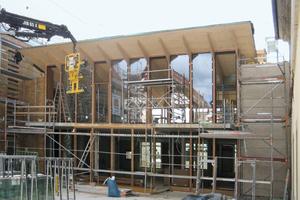Rechts: In die Pfosten-Riegelfassade des transparenten Verbindungsgebäudes werden großformatige Festverglasungen eingebaut