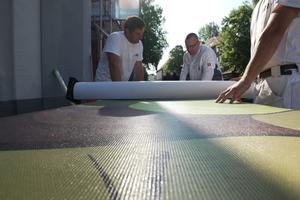 Vorbereitung: Das Motiv des Kastanienbaums, gedruckt auf PhotoVision-Gewebe, wird in Bahnen auf die Baustelle geliefert und zum Anbringen an der Fassade vorbereitet