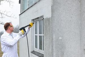 Bevor man den alten Putz schlitzt, wird die komplette Fassade mit einem Dampfstrahlgerät gründlich gereinigt