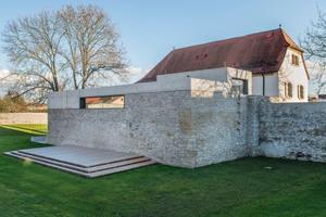Auf den alten Außenmauern der Nebengebäude aus Bruchstein wurde ein Flachdachanbau errichtet, in dem sich die Bibliothek befindet