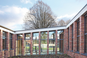 Innenhof mit Mauerwerkspfeilern vor der verglasten Fassade