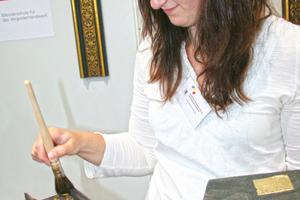 Die Vergoldung tritt durch das Abpinseln des nicht festgeklebten Blattgoldes auf dem Stand der Meisterschule für das Vergolderhandwerk München hervor