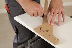 Schablone mit eingestellten Winkel auf die Seitenteile aufsetzen und Bohrlöcher sowie Schnittlinie mit Anreißer anzeichnen