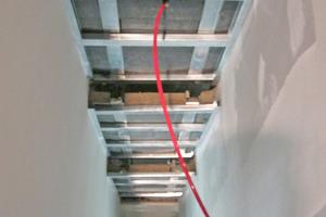 """Zwischen den Baffelreihen wurde jeweils ein abgetreppter, geschlossener Deckenstreifen integriert<span class=""""bildnachweis"""">Foto: TM Ausbau</span>"""