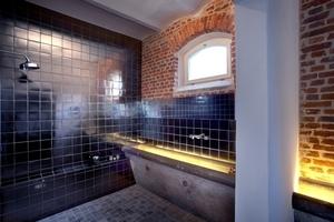 Ehemalige Pferdetröge sind in das moderne Badkonzept eingebunden und dienen heute als Waschbecken