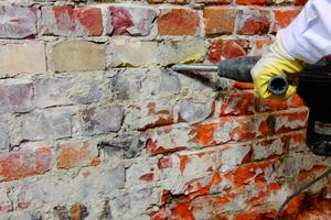Der Handwerker entfernt zu erst den Altputz und räumt die Mauerwerksfugen zirka 2 cm tief aus <br />