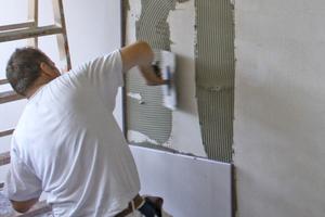 Der Klebemörtel wird mit der Zahntraufel vollflächig auf der Wand aufgetragen