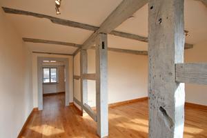 Offenes mit Leinöllasur grau gestrichenes Fachwerk im Obergeschoss
