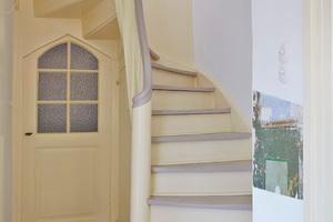 """...und saniert. Die Trittstufen der einfach gewendelten Holztreppe wurden dem Farbkonzept entsprechend im Farbton """"Dove Tale"""" gestrichen. Körper und Tür im Hintergrund, sowie Sockelleisten: """"New White"""". Rechts ist ein Teil einer einfachen Wandmalerei sichtbar Fotos: Linus Weber Denkmalpflege"""