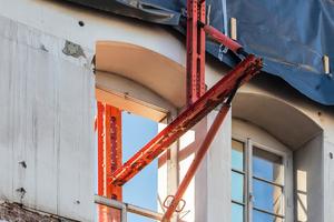 Links: Die exakt an die vorhandenen Fensteröffnungen angepasste Fassadenabstützung basierte auf mietbaren Variokit-Systembauteilen