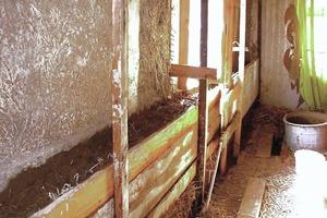 Zwischen der Innenseite einer der Außenwände und einer Brettgleitschalung wird eine Stampflehmwand hergestellt<br />