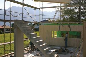 Montage der schweren Massivholzelemente auf der Baustelle. Die Treppe bauten die Handwerker aus Beton – darunter wurde später der moderne Scheitholzofen eingebaut<br />