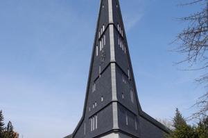 Denkmalgeschützte Kirche in Lahntal/Sarnau bei Marburg aus den 60er Jahren des 20. Jahrhunderts. Die poröse Oberflächenstruktur vor der Instandsetzung weist auf Verarbeitungsfehler hin. Um das vom Architekten gewollte Erscheinungsbild zu erhalten, wurden Brettmuster aufgedrückt, die nach der Instandsetzung den schalungsrauen Beton imitieren sollen<br />