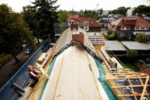 Blick von oben auf die bereits gedämmte Gaube (rechts) und den vollständig gedämmten ersten Bauabschnitt. Laufende Dämmarbeiten am zweiten, mittleren Gebäudeteil