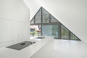 """Küche der Wohnung im Dachgeschoss mit komplett verglastem Dachgiebel hinter einer unregelmäßig ornamentierten Holzverschalung<span class=""""bildnachweis"""">Foto: Architekturfotografie Sabrina Scheja</span>"""