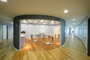 Im Büro- und Trainingscenter Hallbergmoos ist der Coffee-Shop zentraler Treffpunkt. In den runden Wandkörpern sitzen große Wandöffnungen und Türen
