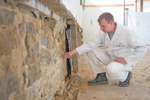 Begutachtung des vormals von einer Bitumenbahn abgedeckten Kalksandsteinmauerwerks der Scheune
