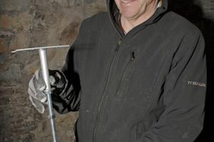 Martin Maassen erklärt seine Hohlraumbodenstütze, deren Füße über eine etwa 30 cm lange Gewindestange in ihrer Höhe präzise eingestellt werden können
