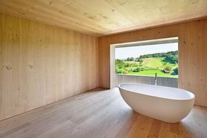 """Die allseitig mit Holz verkleideten """"Kammern"""" der Wohnungen bilden einen starken Kontrast zu den weitläufigen, ganz in weiß gehaltenen offenen Räumen (siehe großes Foto auf voriger Seite)<span class=""""bildnachweis"""">Foto: Architekturfotografie Sabrina Scheja</span>"""