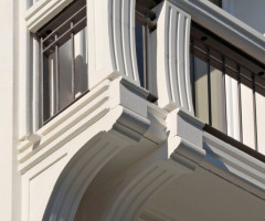 Geschwungene Konsolen binden die Balkone stilistisch in den gründerzeitlichen Fassadenschmuck ein
