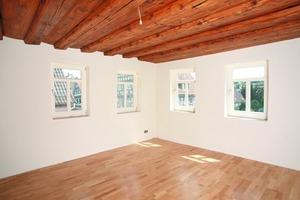 Das Ergebnis der Innendämmarbeiten: eine homogene weiße Wandfläche zwischen der historischen Holzdecke und den neuen geölten Massivholzdielen<br />