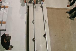 Rechts: Die Laminam-Großformatfliese mithilfe von Vakuumschienen ins Mörtelbett heben