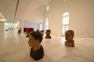 Künstlerische Installation mit Holzköpfen vor dem Zugang zum Plenarsaal