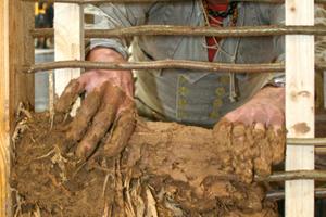 Der Berliner Maurermeister Andreas Joerdens beim Ausfachen eines Weidengeflechts mit einer Stohlehmmischung