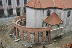Das Mauerwerk für den Anbau wird von den Handwerkern in einem weiten Bogen um den Chor gezogen