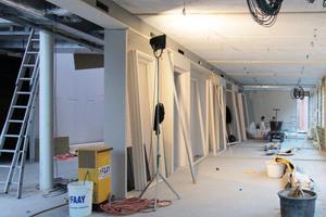 Im Neubau der Firma Faay werden durch die Doppelfunktion der Trennwand zur Büroseite hin Wandregale geschaffen