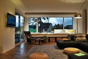 Das Wohnzimmer des Bungalows öffnet sich mit großen Fenstern zum Garten hin<br />