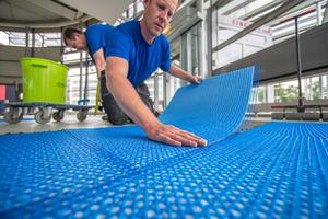 Die Entkopplungsmatten werden mit der Vliesseite nach unten in ein Bett aus Fliesenkleber gelegt und angedrückt. Das überstehende Glasgittergewebe dient zur Überlappung der Stöße<br />Fotos: Blanke