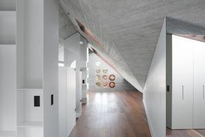 Puristische Materialkombination: Wände und Decken aus Sichtbeton, ein Bodenbelag aus Sipo-Mahagoni-Holz und weiß lackierte Einbaumöbel