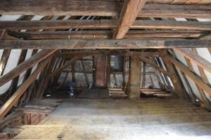 Dachstuhlansicht vor Instandsetzung. Sichtbare Hilfsabstützungen und neue Ziegelwand zum Nachbargebäude hin<br />