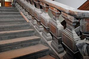 Schmuckvolles Geländer einer Holztreppe vor der Sanierung <br /><br />